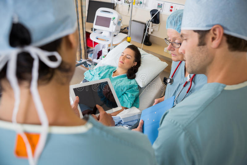 Verpleegsters en Patiënt in Postop Eenheid in het Ziekenhuis stock afbeelding