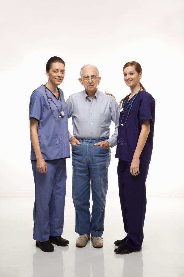 Verpleegsters met bejaard mannetje. stock afbeelding