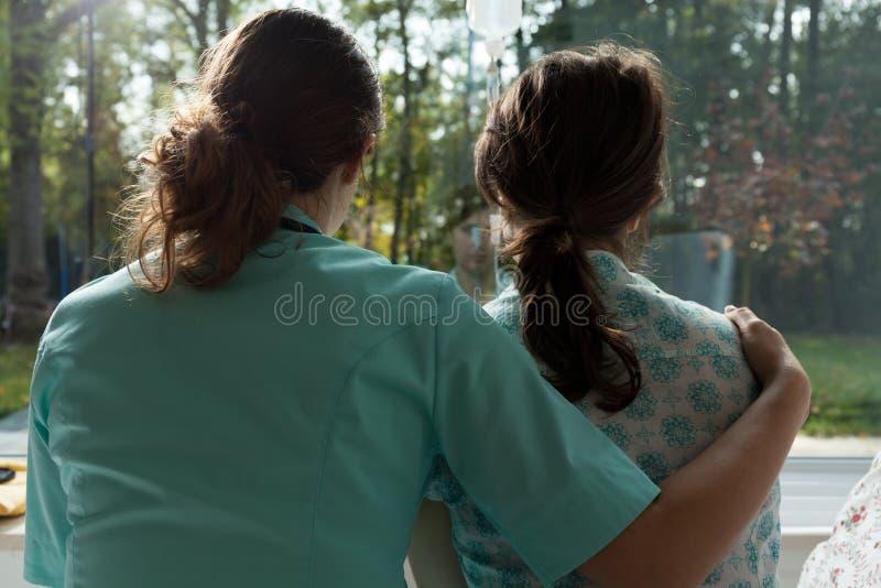 Verpleegsterszorgen voor droevige patiënt stock foto's