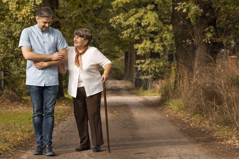 Verpleger ondersteunend gelukkige vrouw met wandelstok in het bos stock fotografie