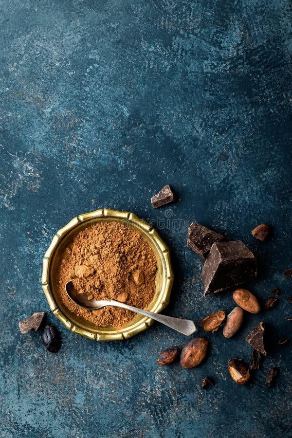 Verpletterd cacaopoeder, bonen en donkere chocoladestukken, culinaire achtergrond royalty-vrije stock afbeelding