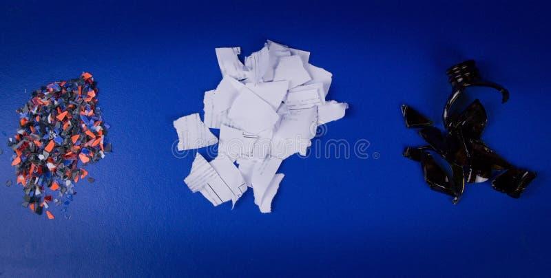 Verpletterd plastiek, stukken van gescheurd document en gebroken donker glas op een blauwe achtergrond stock afbeeldingen