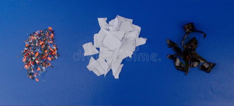 Verpletterd plastiek, stukken van gescheurd document en gebroken donker glas op een blauwe achtergrond stock fotografie