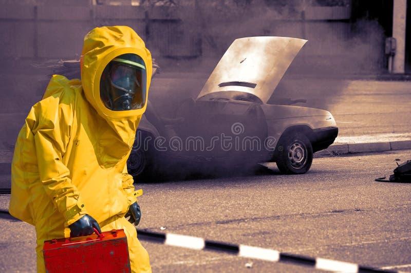 Verpletterde auto en mens met aktentas in beschermend hazmatkostuum stock foto's