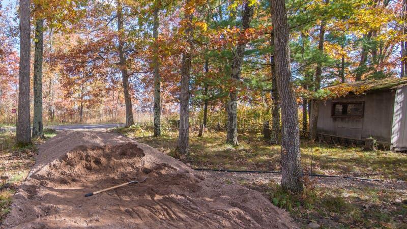 Verpletterde rotsstapel met schop met rustieke loods op achtergrond - landelijk weg en het lopen wegproject in een mooie kleurrij stock afbeeldingen