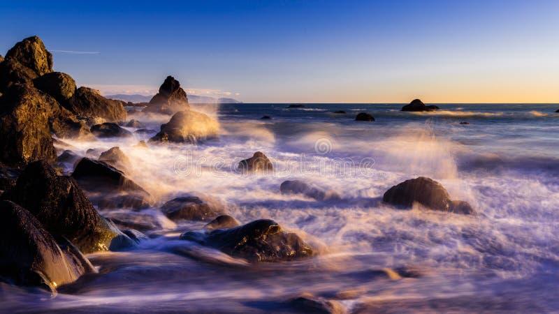 Verpletterende golven bij het dromerige strand van Californië bij zonsondergang stock afbeelding