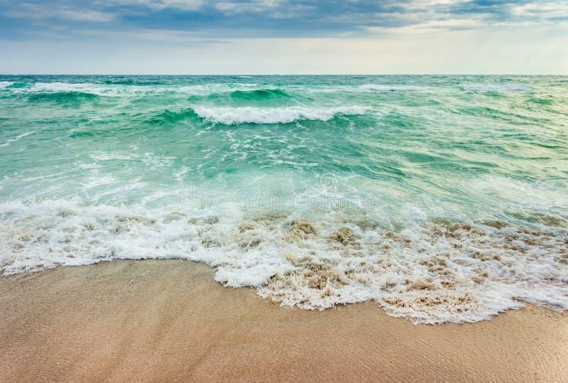 Verpletterende golven op zandig strand stock foto