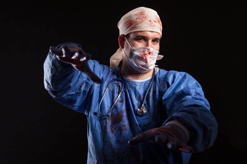 Verrückt behandeln Sie mit einer Chirurgmaske und scheuert bespritzt mites Blut für Halloween stockfotos
