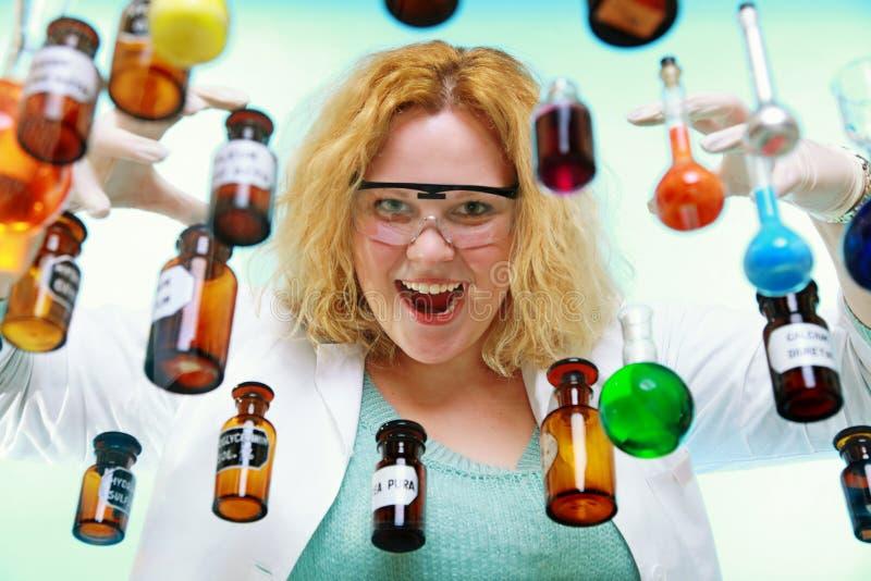 Verrückte Chemikerfrau mit chemischer Glaswarenflasche lizenzfreie stockfotografie