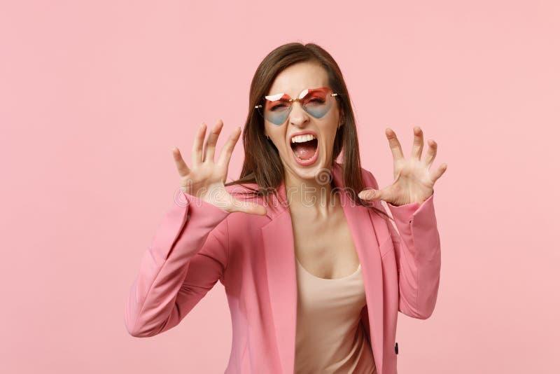 Verrückte junge Frau im schreienden Knurren der Herzgläser wie dem Tier, Katzengreifergeste lokalisiert auf Pastellrosa machend stockfoto