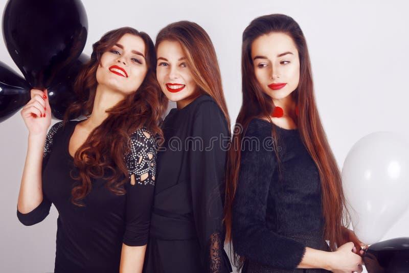 Verrückte Parteizeit von drei schönen stilvollen Frauen im zufälligen schwarzen Kleid des eleganten Abends feiernd, den Spaß habe lizenzfreie stockbilder