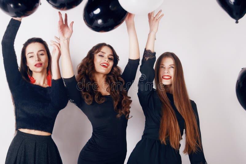 Verrückte Parteizeit von drei schönen stilvollen Frauen im zufälligen schwarzen Kleid des eleganten Abends feiernd, den Spaß habe stockfoto