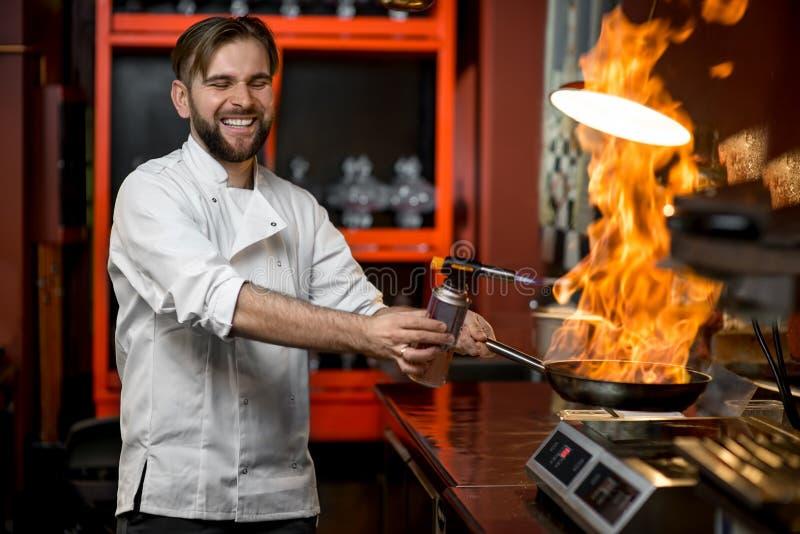 Verrückter Chef, der mit großem Feuer auf der Bratpfanne kocht stockbild