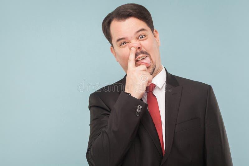 Verrückter dummer Geschäftsmann, der eine ` s Nase auswählt stockbilder