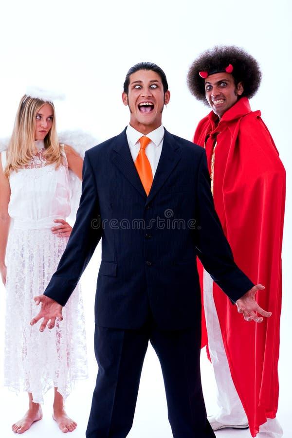 Verrückter Geschäftsmann mit Engel und Dämon lizenzfreie stockfotos