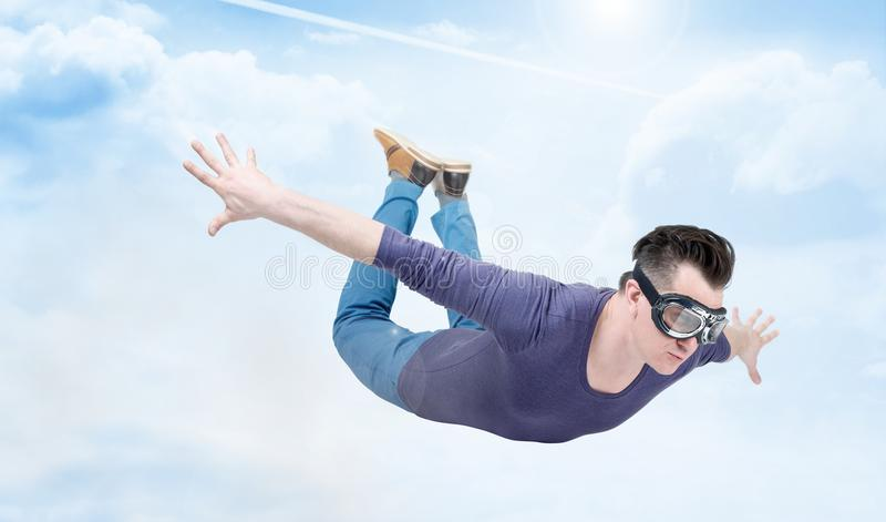 Verrückter Mann in den Schutzbrillen fliegt in den bewölkten Himmel Pulloverkonzept stockbild
