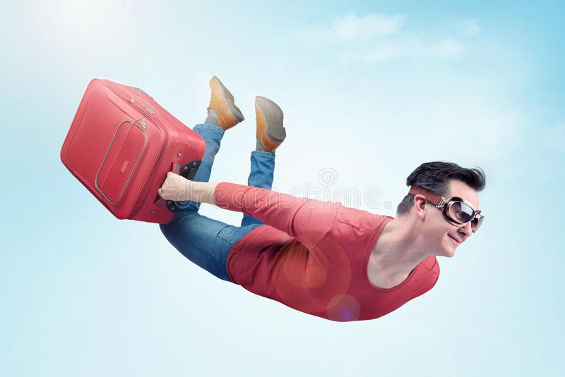 Verrückter Mann in den Schutzbrillen und mit rotem Koffer fliegt in den Himmel Konzept von Ferien lizenzfreie stockfotos