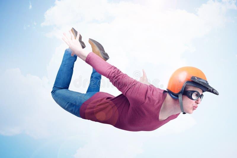Verrückter Mann im roten Sturzhelm und in den Schutzbrillen fliegt in den Himmel Pulloverkonzept lizenzfreies stockbild