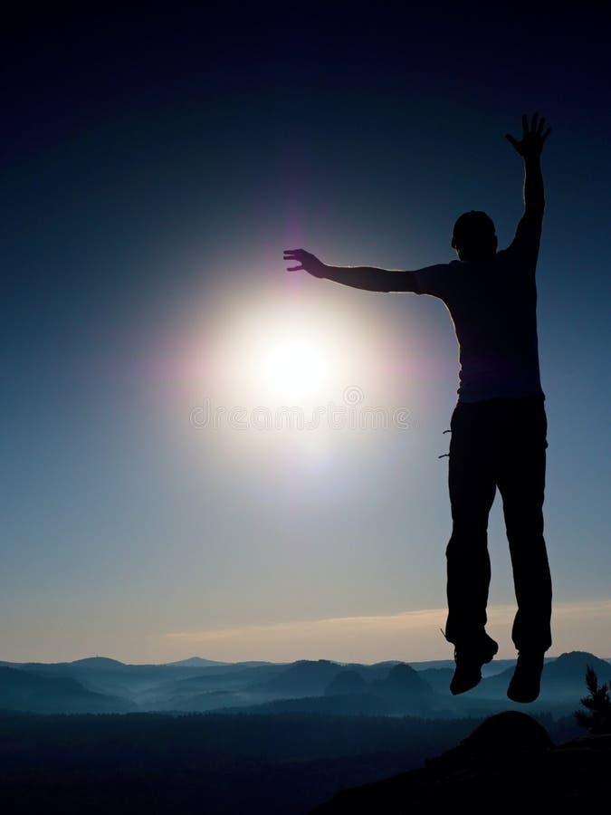 Verrückter Mann springt auf Berg Schattenbild des springenden Mannes und des schönen Sonnenunterganghimmels stockfotos