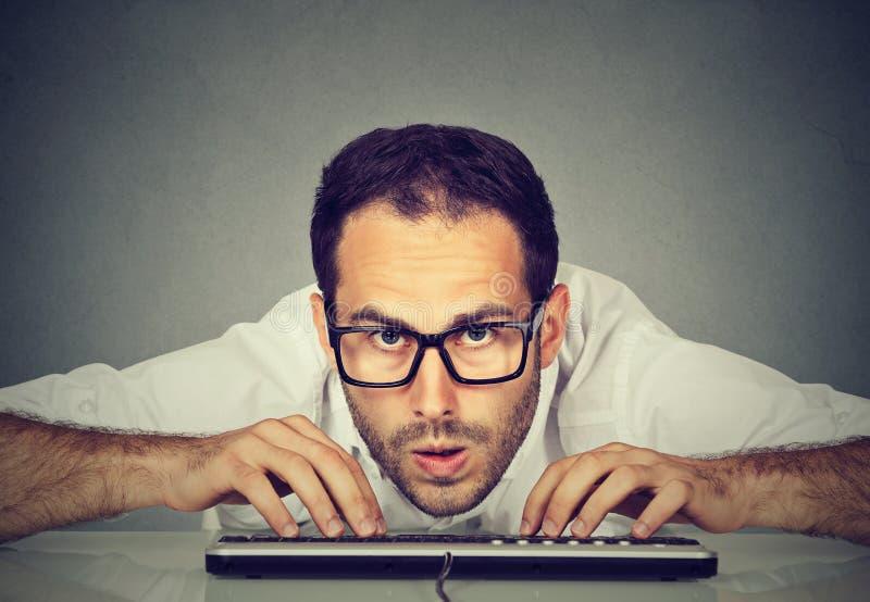 Verrückter schauender nerdy Mann, der auf Tastatur schreibt lizenzfreies stockfoto