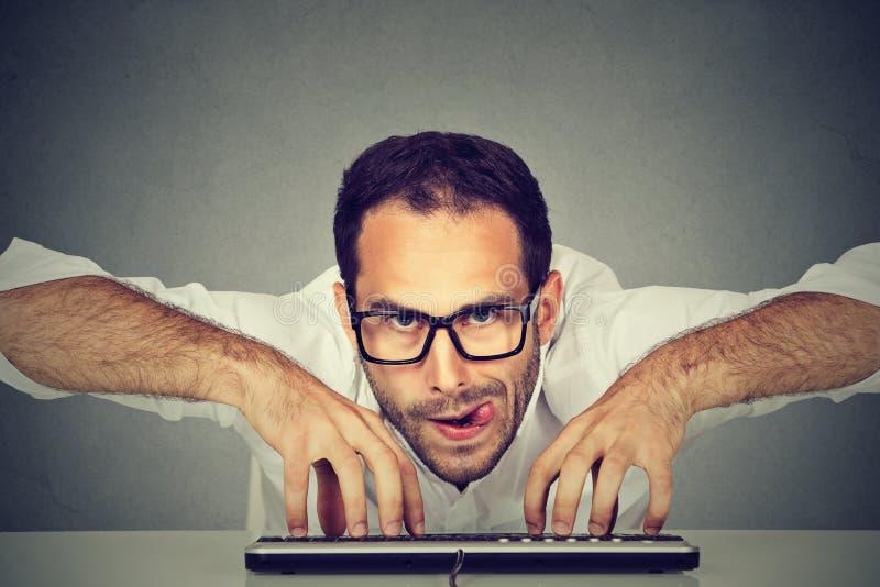 Verrückter schauender nerdy Mann, der auf Tastatur schreibt lizenzfreie stockfotos