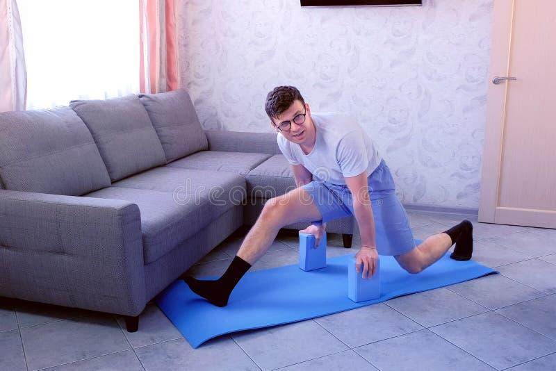 Verrückter Sonderlingsmann versucht, die Spalten auf der Matte das erste mal zu tun zu Hause Sportstimmungskonzept stockbild
