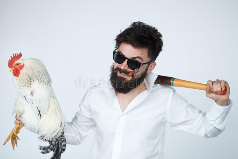 Verrückter und lustiger Mafiachef, der einen Hahn hält stockbild