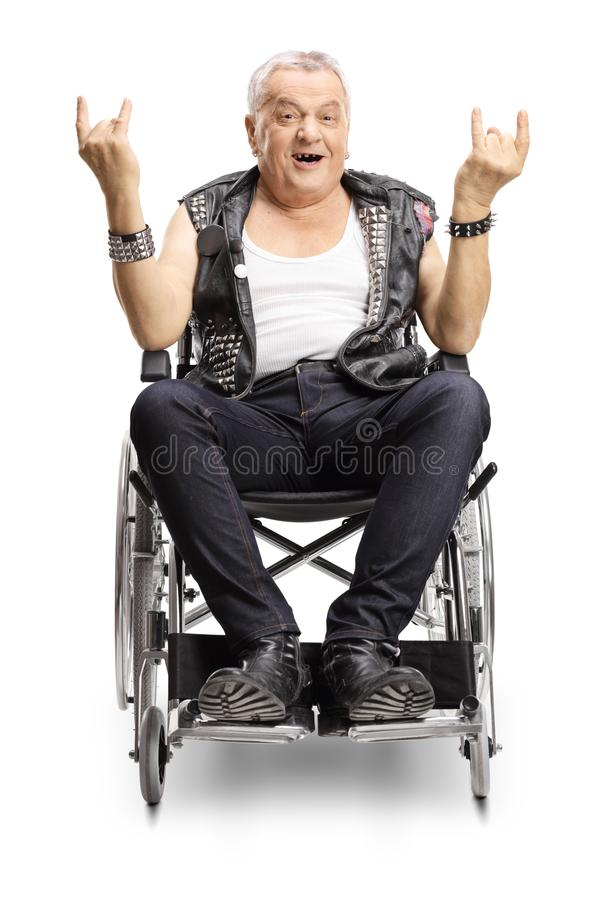 Verrücktes älteres männliches punker in einem Rollstuhl, der ein Hornzeichen macht stockfotografie
