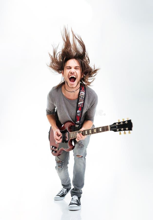 Verrücktes Rütteln des jungen Mannes Haupt und Spielen der E-Gitarre lizenzfreies stockbild