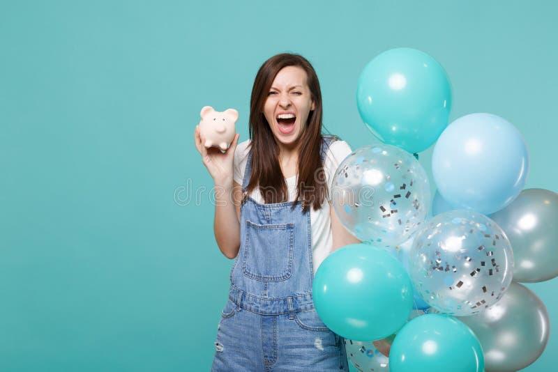 Verrücktes schreiendes lustiges junges Mädchen in der Denimkleidung, die piggy Geldbank feiernd mit bunten Luftballonen hält lizenzfreies stockfoto