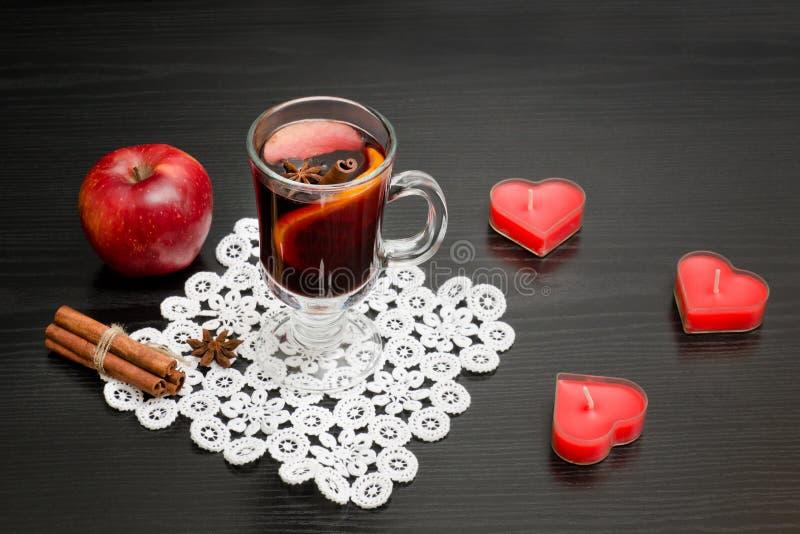 Verrührter Wein mit Gewürzen Kerzen in Form eines Herzens, cinnam lizenzfreies stockfoto