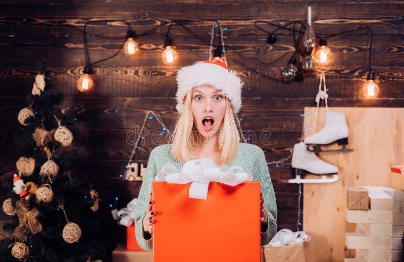 Verrassing De Kerstmiswensen komen waar als u gelooft Kerstmis huidige gift De emotionele verraste vrouw verheugt zich heden stock afbeeldingen