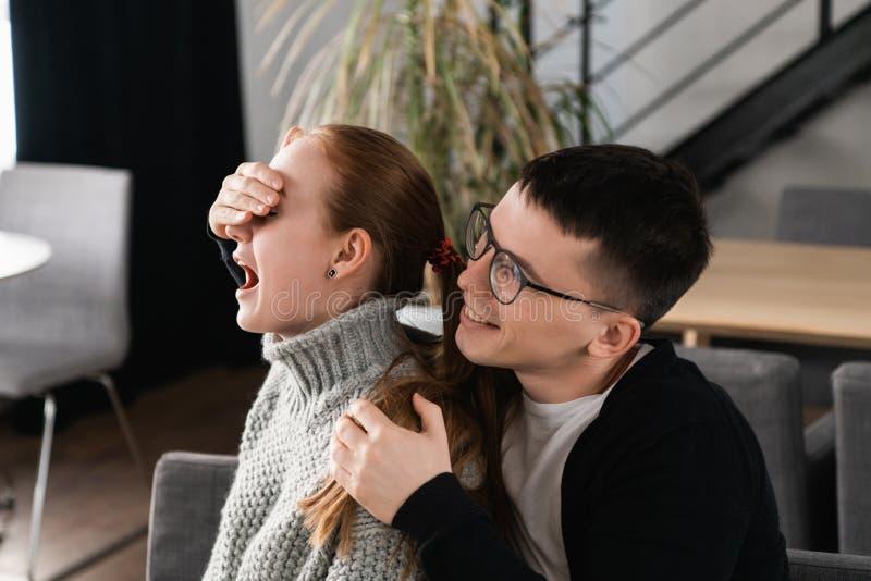 Verrassings Mooi romantisch paar in koffie De mens behandelt de ogen van zijn meisje terwijl zij die op een verrassing wachten stock afbeelding