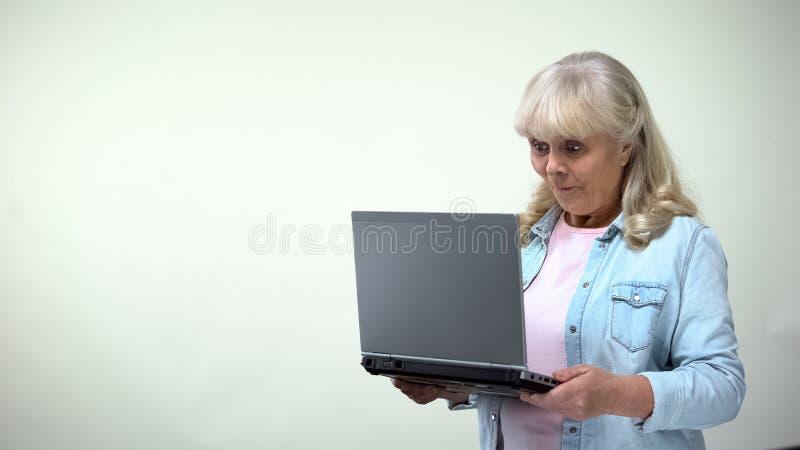 Verrast bejaard vrouwelijk lezingsbericht op laptop, goed nieuws, mededeling royalty-vrije stock foto