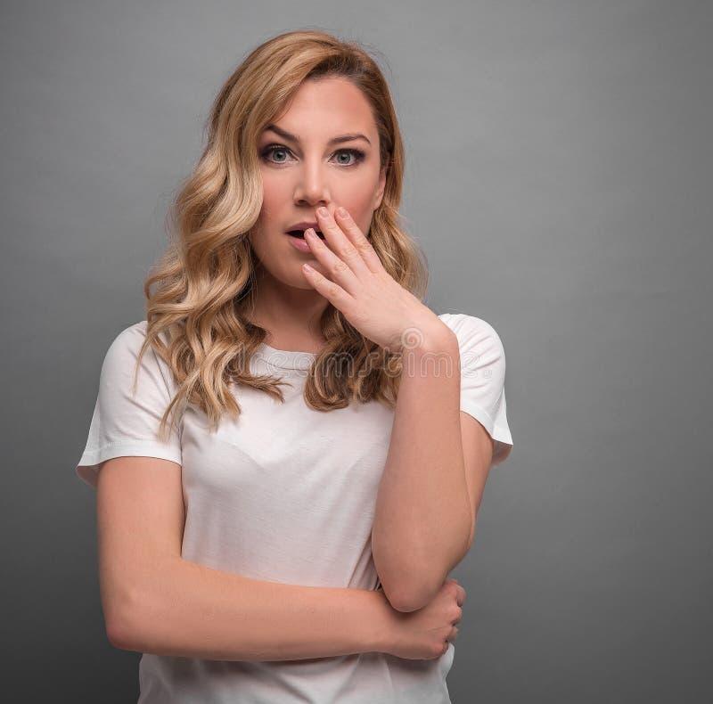 Verrast blonde op een grijze achtergrond royalty-vrije stock foto's