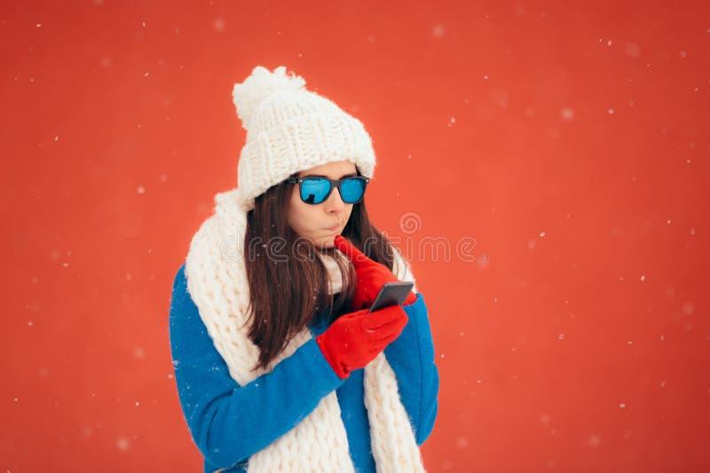 Verrast de Wintermeisje die Haar Smartphone controleren royalty-vrije stock fotografie