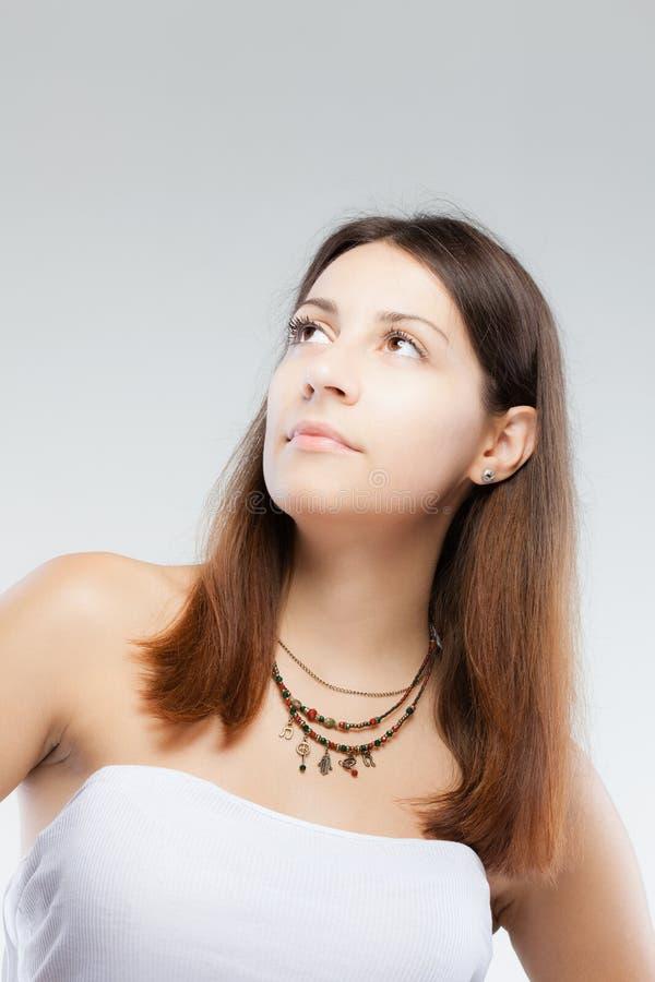 Verrast donkerbruin meisje die een halsband met generische symbolen dragen royalty-vrije stock fotografie