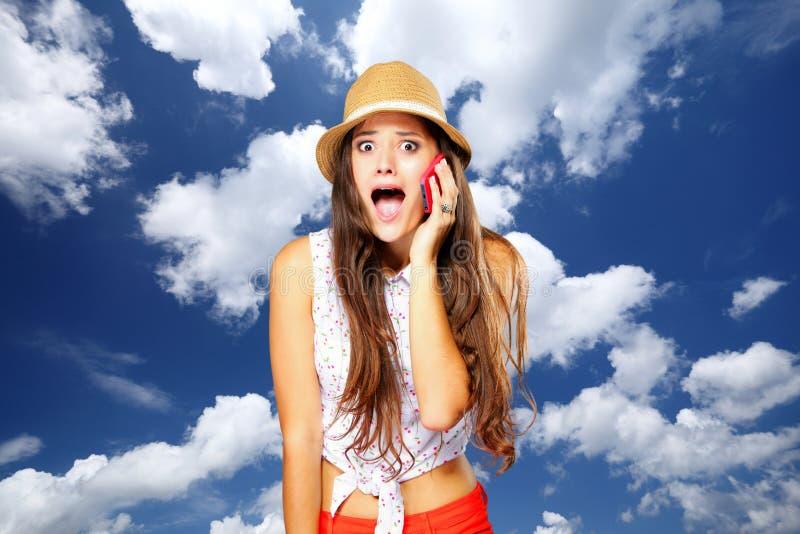 Verrast emotioneel meisje die op mobiele telefoon spreken. Hemelachtergrond. royalty-vrije stock foto