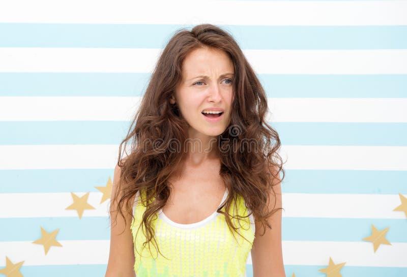 Verrast emotioneel meisje met lang krullend haar het meisje kijkt onzeker betwijfel uitdrukking en verwar van vrouw met lang stock fotografie