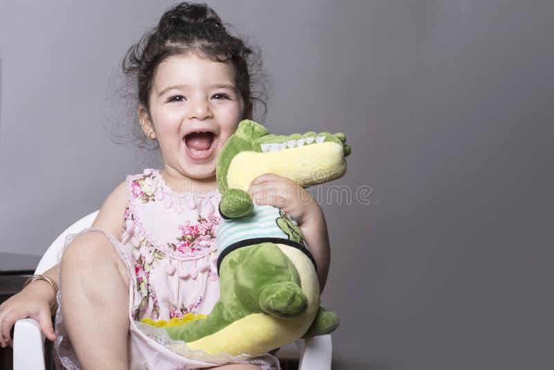 Verrast en gelukkig meisje die een krokodillepop houden op goedkope plastic stoel gezet royalty-vrije stock foto
