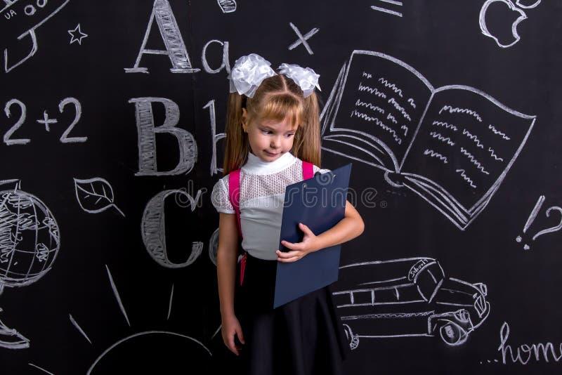 Verrast en teleurgesteld schoolmeisje die zich vóór het bord als achtergrond met een roze terug rugzak op haar bevinden stock fotografie