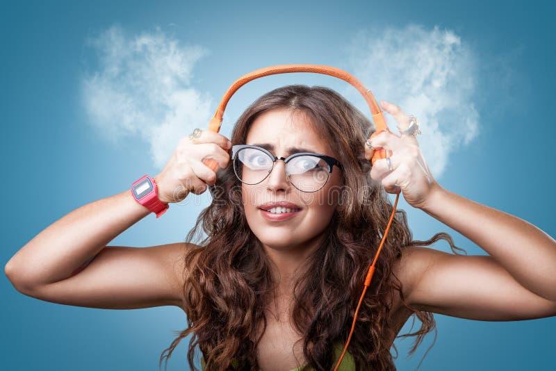 Verrast geïmponeerd meisje die in hoofdtelefoons aan muziek luisteren royalty-vrije stock afbeelding