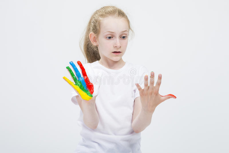 Verrast Jong Meisje die Slordige Kleurrijke Handen bekijken die helder tijdens Verfambacht worden geschilderd Tegen wit stock fotografie