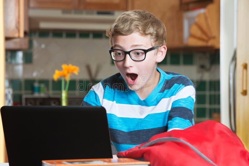Verrast kind die laptop computer met behulp van stock afbeelding