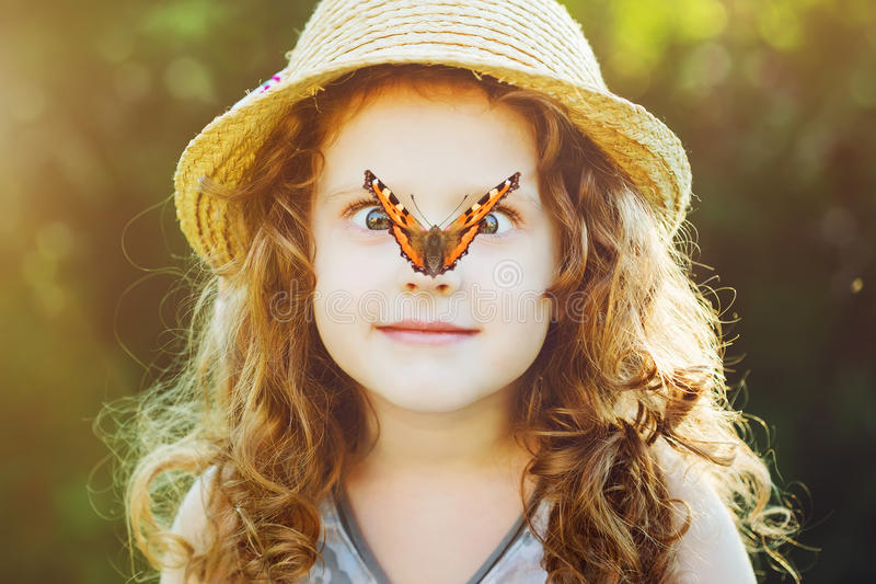 Verrast meisje met een vlinder op haar neus Het stemmen aan instagram stock foto's