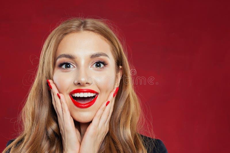 Verrast meisjesgezicht op rode achtergrond Het gelukkige portret van de vrouwenclose-up royalty-vrije stock afbeeldingen