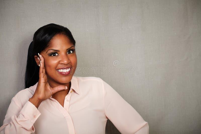 Verraste Afrikaanse vrouw die bij de camera glimlachen stock foto's