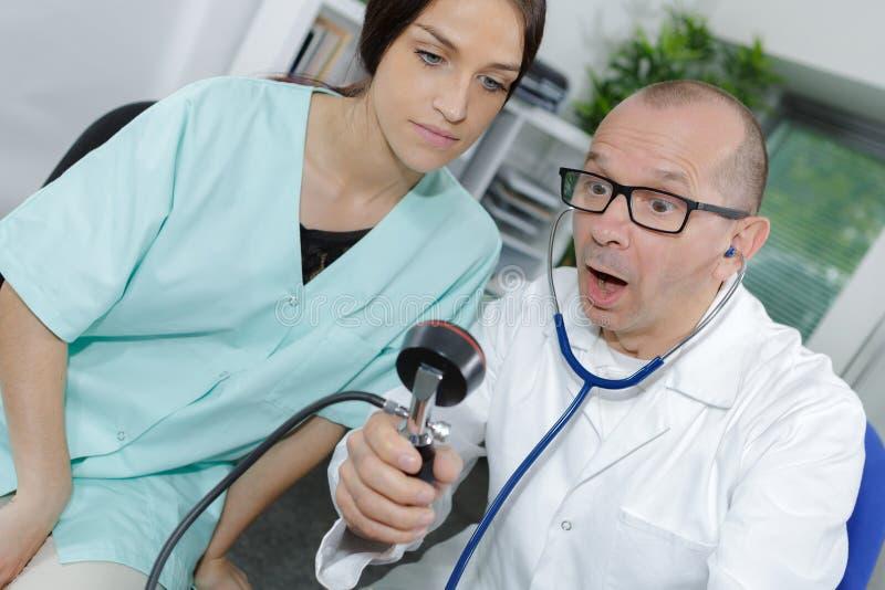 Verraste arts met bloeddrukmonitor stock afbeeldingen
