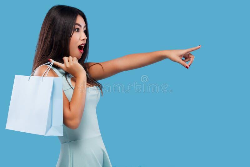 Verraste Aziatische vrouw bij het winkelen holdingszak en punten omhoog op exemplaarruimte Geïsoleerd op blauwe achtergrond op zw stock foto's