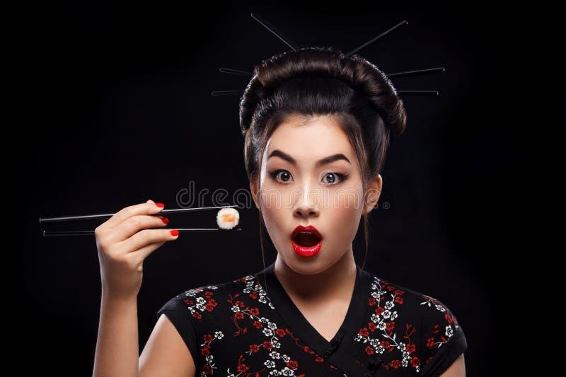 Verraste Aziatische vrouw die sushi en broodjes op een zwarte achtergrond eten stock fotografie